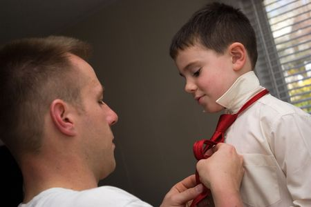 getting late: A young dad helps his son get ready by helping him tie his neck tie.
