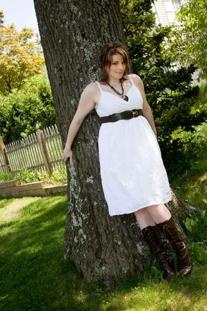 A young attractive woman in a white dress leaning against a tree trunk. photo