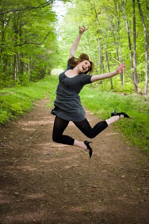 A young woman joyously jumping in the air in a wooded setting. photo