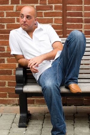 A man in his twenties sitting casually on a bench in an urban area. Imagens - 6048673