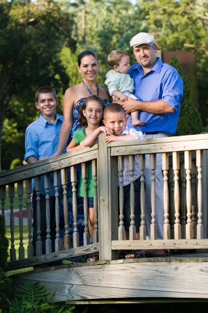large family: Portrait of an attractive young family with four children posing in a park on a wooden walking bridge. Stock Photo