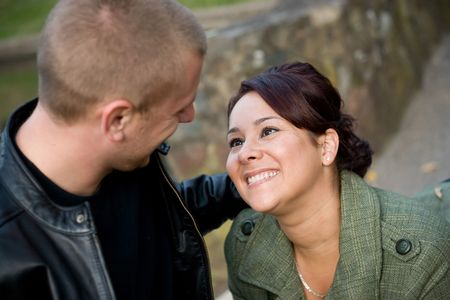 A young happy couple looking fondly at one another outdoors.  Shallow depth of filed with focus in the woman. photo