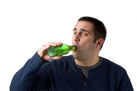 alcoholic drink: A young man drinking a bottle of beer isolated over a white background.