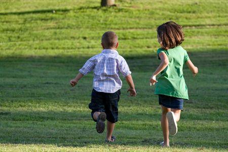 ni�o corriendo: Un poco de chico y chica se ejecutan a trav�s del campo de c�sped sin una atenci�n en el mundo.