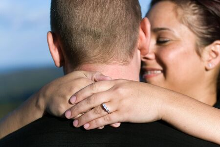 A young happy couple that just got engaged.  Shallow depth of field with focus on the diamond engagement ring. photo