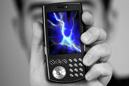 radiacion: Un hombre tiene un tel�fono celular con una ilustraci�n de perno de rayo en la pantalla.  Excelentes im�genes para ilustrar la radiaci�n de tel�fono celular.