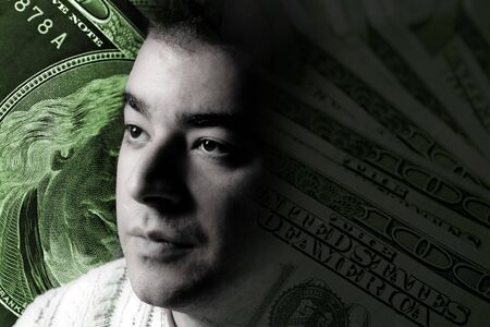 A young man with money on his mind.  A great image to illustrate unemployment or stock investments. photo