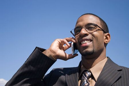 A young business man talking on his cell phone where he has service. photo