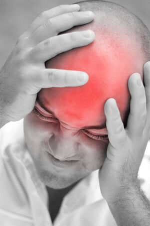 illustrates: A young man grips his head in agony.  The red highlighted area illustrates his head pain. Stock Photo