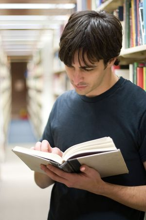 A young man reads a book at the library while standing in the aisles of book shelves. photo