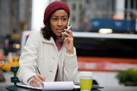 conversa: Una mujer de negocios m�viles en las conversaciones de ciudad en su tel�fono celular mientras escribiendo algo en su Bloc de notas.