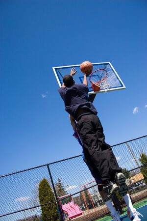 A young basketball player shoots the basketball at the hoop. Stock Photo - 6155882