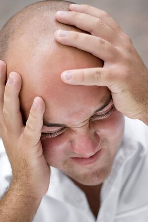 A young man that looks to be upset and grabbing his head in pain or anguish. photo