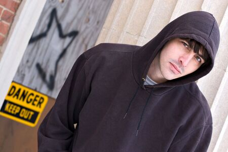 tough: A tough looking guy posing in a grungy urban setting in a hooded sweat shirt. Stock Photo