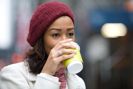 winter break: A modern business woman in the city  enjoying a cup of coffee hot chocolate latte or tea.