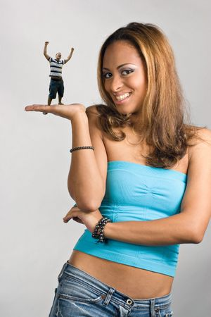 shrunken: A young woman holding a miniature young man in her hand.