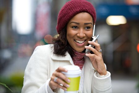 A modern business woman in the city talks on her cell phone while enjoying a cup of coffee. photo