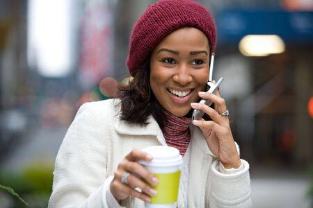 conversa: Una mujer de negocios modernos en las conversaciones de ciudad en su tel�fono celular mientras que goza de una taza de caf�.