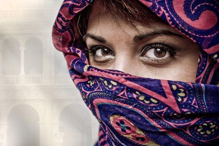 Een aantrekkelijke midden-Oosterse vrouw draagt een kleurrijke muurkop.  Stockfoto