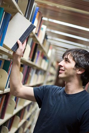 A young man pulling a book from the shelf at the library. photo