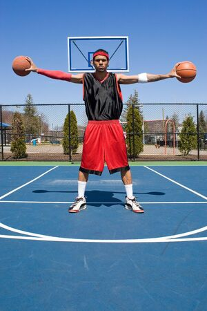 basketballs: A young basketball player palming two basketballs.