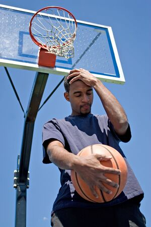 Basketball player holding his head in disappointment over losing the game. photo