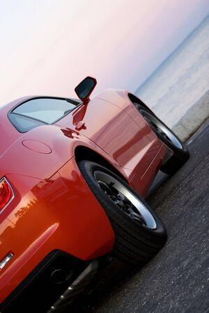 rental: A modern sports car parked at the beach around sunset.