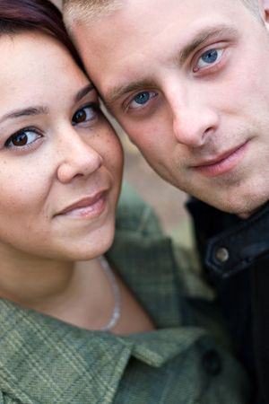 Closeup of a young happy couple together.  Shallow depth of field. photo