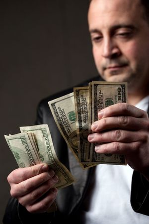 A crooked looking man counting a handful of one hundred dollar bills. Shallow depth of field. Stock Photo - 6268127