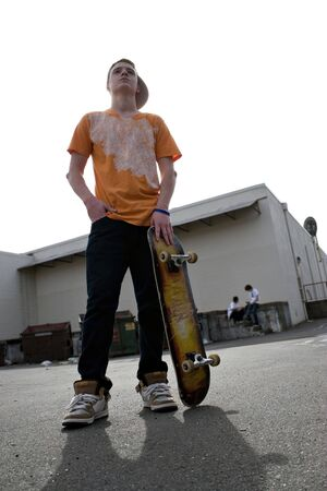 emo: A young teenage skateboarding standing with his skateboard and other kids hanging out in the background.