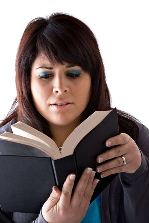 A young woman reading a book with a concerned expression on her face. Stock Photo - 6285768