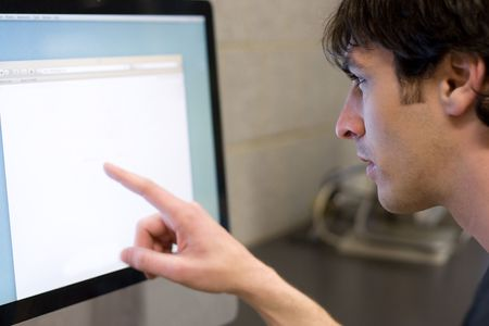 the strongest: A young man pointing at a modern computer monitor lcd with copyspace.  Shallow depth of field with strongest focus on the face.