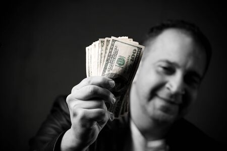 A happy man holds a handful of cash with selective color. photo