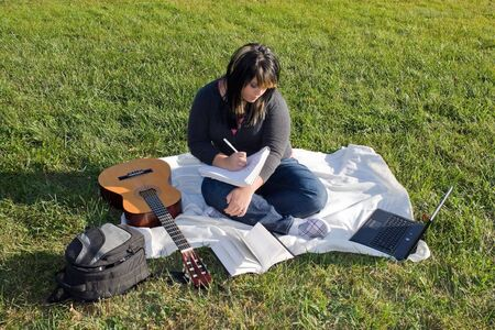 A young female singer or song writer with her guitar and computer outdoors in the grass. photo
