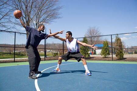 A young basketball player guarding his opponent during a one on one basketball game. Stock Photo - 6315799
