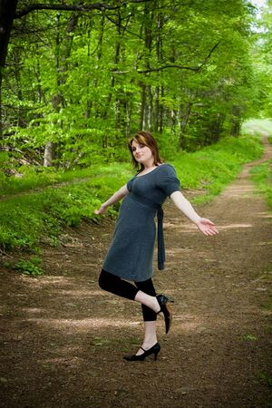 frolic: A young woman posing on a wooded path.