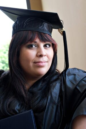 A young hispanic woman wearing her cap and gown on graduation day. photo