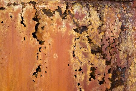 flaked: A rotted metal panel covered in rust.