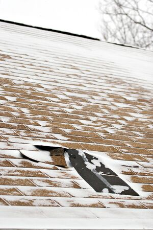 damages: Damaged roof shingles blown off a home from a windy winter storm with strong winds.
