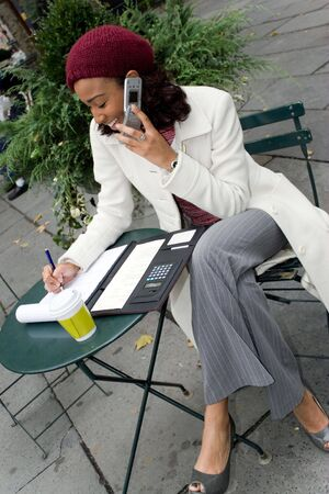 A successful career woman conducting business outdoors at a table with her cell phone and coffee. photo