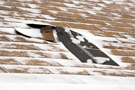 Damaged roof shingles blown off a home from a windy winter storm with strong winds. photo