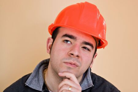 hard: A young construction working with a pensive or contemplative look thinking hard about something.