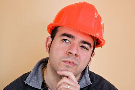 Una construcción de jóvenes trabajando con una mirada contemplativa o pensativa pensando duro sobre algo. Foto de archivo - 6504212
