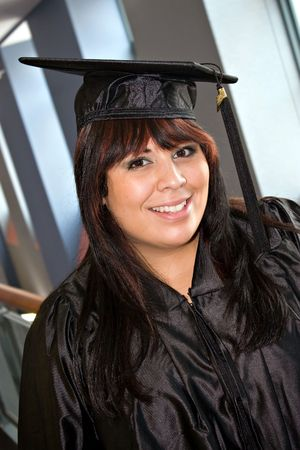 recently: A woman that recently had a school graduation posing in her cap and gown indoors.