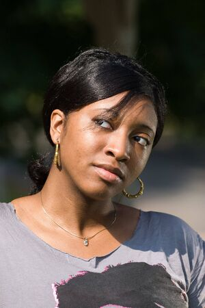 An attractive young Jamaican woman with a contemplative look on her face. photo
