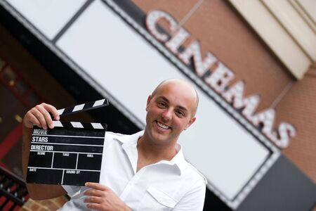 A production assistant or movie director holding a clap board or slate in front of the cinemas. photo