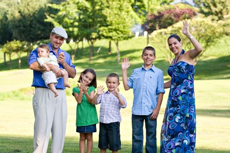 Portrait of an attractive young family with four children waving happily. Stock Photo - 6504216