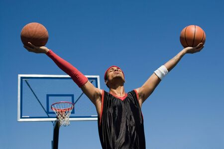 baller: A young athletic build basketball player holding up two basketballs in the air.