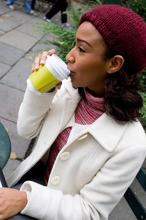 sorbo: Una mujer de negocios joven toma un sorbo de su caf� caliente o otra bebida.  Foto de archivo