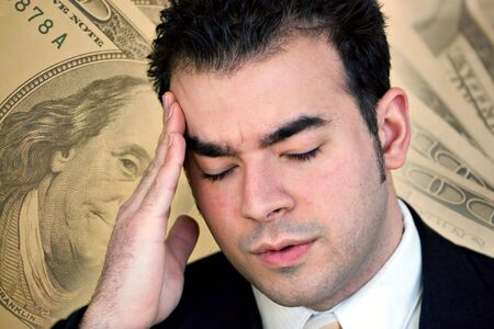 layoffs: A man with a headache from all of the stress of his financial problems.